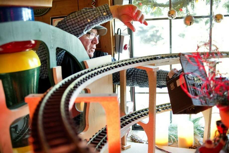 NICK KING | nking@mdn.netTom Valent arranges buildings donated by the Church family into his toy train display at the Santa House.