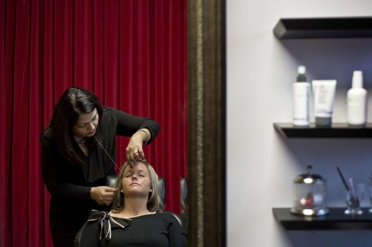 SEAN PROCTOR | sproctor@mdn.netFarah Shahid, of Bay City, owner of the Pomegranate Salon on North Jefferson Avenue, works on threading Meaghan Alberts' eyebrows.