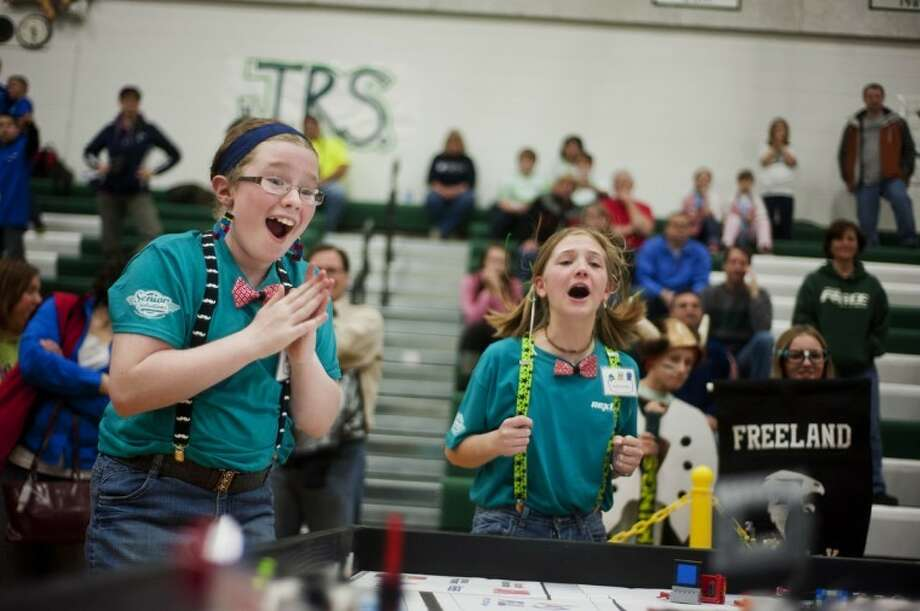 "Zack Wittman | for the Daily NewsFreeland students Chloe Schaller, 11, and Eleanor Knudson, 10, of ""Team Freeland Frenzy"" react to their robot's success during a match at the Elementary Robotics Tournament at Freeland High School on Saturday."