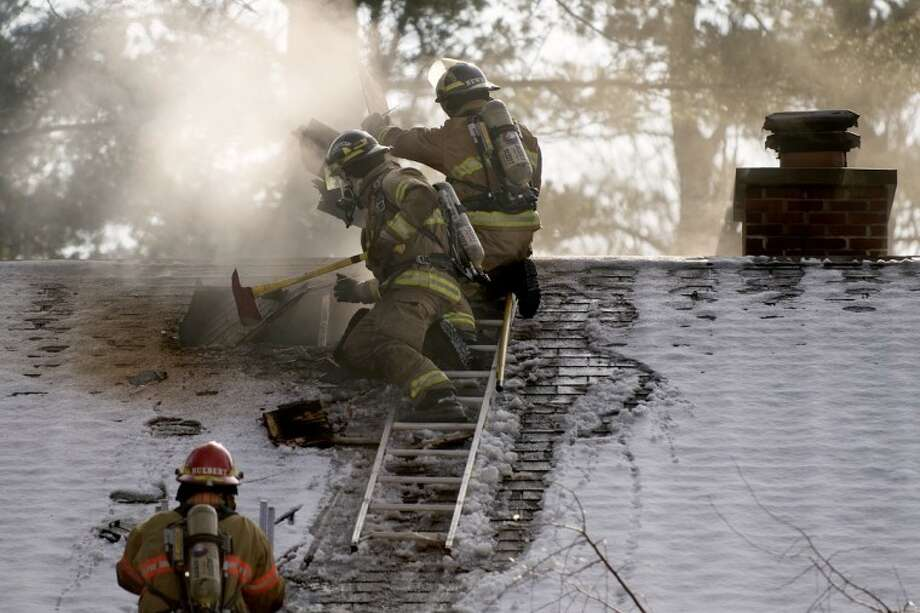 NEIL BLAKE | nblake@mdn.netMidland firefighters cut through roof singles at a home at 2113 Sylvan Lane after a fire there today. Photo: Neil Blake/Midland  Daily News