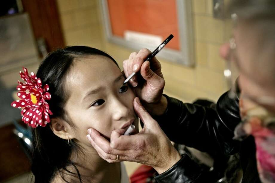 SEAN PROCTOR | sproctor@mdn.netTherese Joffre, 10, looks up at her mother, Kathy, as she applies makeup before dancing the Cumbia, a Colombian dance, with other members of her Adams Elementary class during Fiesta Hispana at Central Middle School. The event, organized by Midland Public Schools, brings elementary Spanish teachers and community members together for an evening to share their countries and cultures with Midland fifth-graders. Photo: Sean Proctor