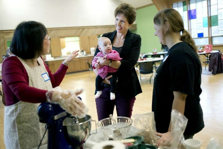 NICK KING | nking@mdn.netYoungLives coordinator Susan Marsh, center, talks with Nilsa Takamori, left, and Latosha Tetreau, 18, right, while holding Latosha's 3-month-old daughter Ashlynn during the 'Make, Take and Bake Young Lives FUNdraiser' Friday at the Midland Reformed Church. Takamori and Latosha were making spiced cookies. Photo: Nick King/Midland  Daily News