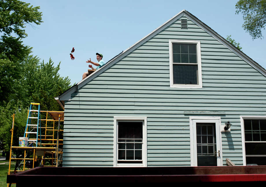 Matt Bender, 18, of Midland, catches roofing gloves from Larry Clark while laying tarpaper on Katie Cook's roof Tuesday afternoon. Photo: Brittney Lohmiller / Midland Daily News