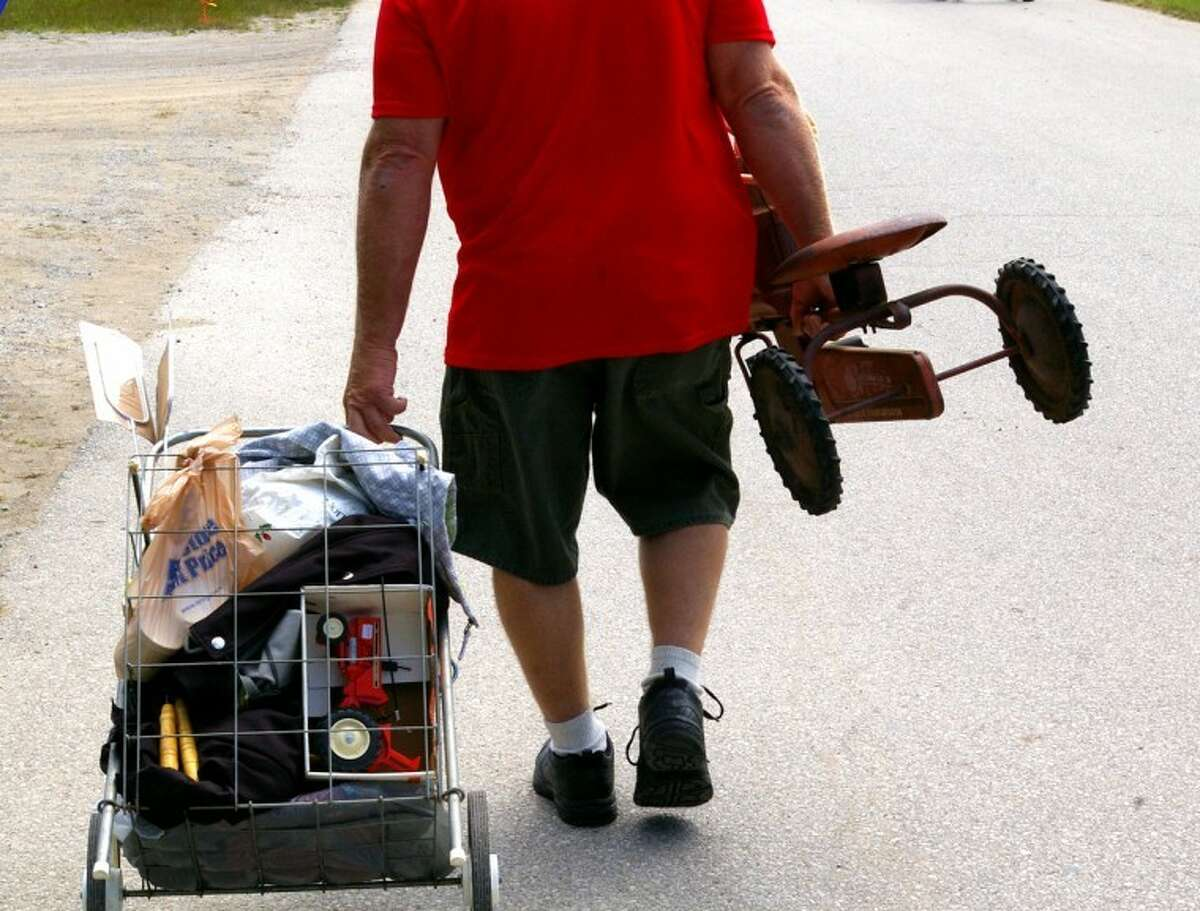 Stuart Frohm   for the Daily NewsA shopper from Ontario leaves on Sunday, carrying a pedal tractor and pulling other items.