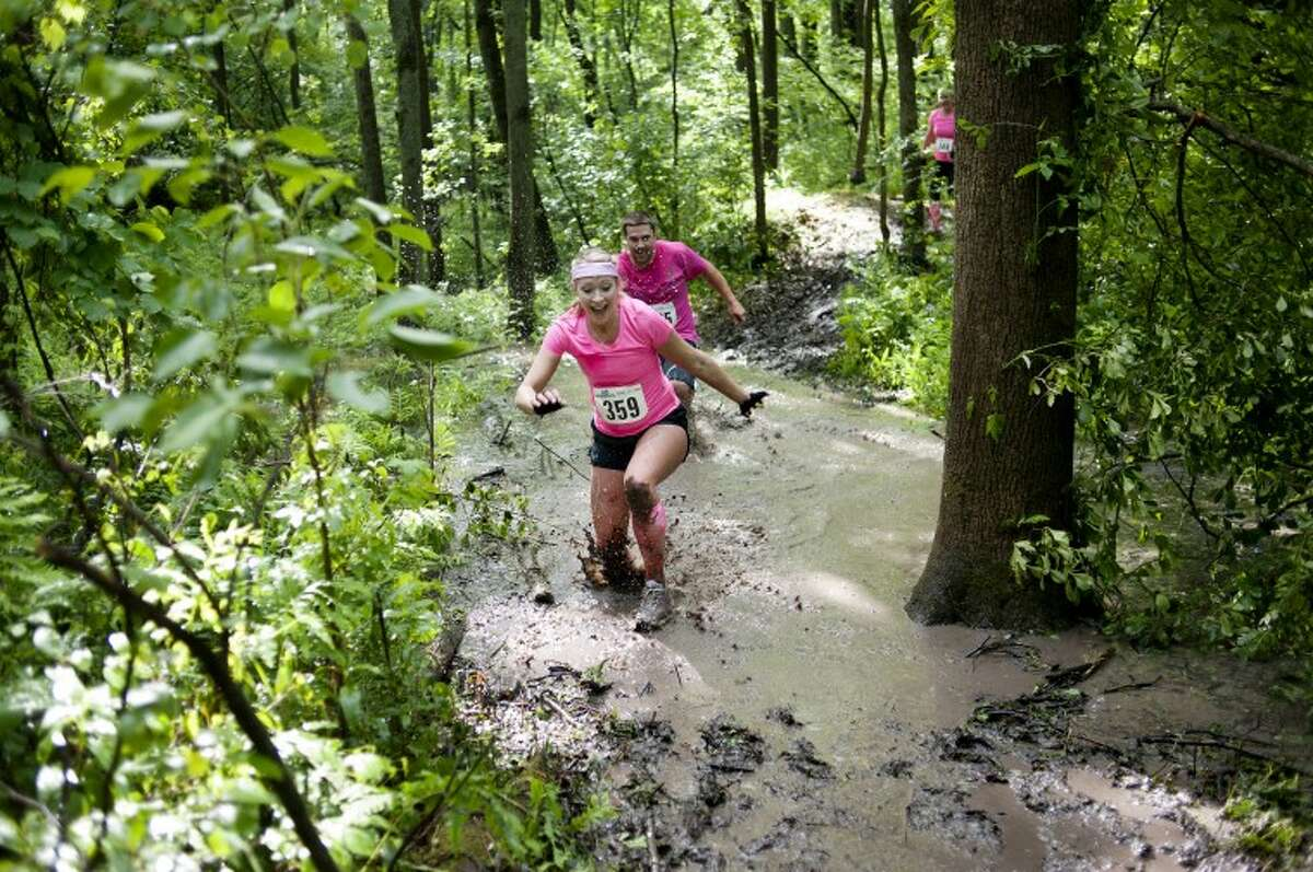 """NEIL BLAKE   nblake@mdn.netJessica Sherman, front, of Petoskey and Matt Zulski of Pellston run through a muddy portion of the alphARace course at City Forest in Midland on Saturday. """"It was tough,"""" Zulski said. """"But once you got to a certain amount of pain, you can just do it."""""""