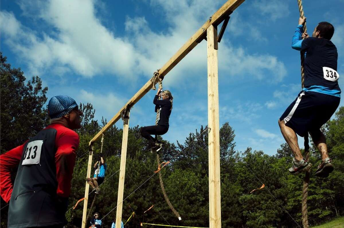 JAKE MAY   for the Daily NewsKarlie LeRoy of Saginaw, center, finishes the rope climb as Rick Hodges, left, of Midland, catches his breath while watching Amir Malekadeli of Midland and other competitors climb rope during an obstacle on Saturday morning at thealphARace at City Forest in Midland.
