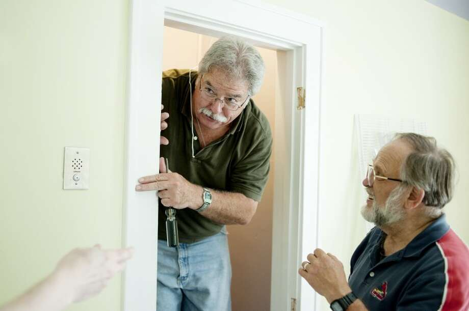 NEIL BLAKE | nblake@mdn.netKent Southworth, left, of Midland, peeks out from a doorway as he and Jim Morrone of Midland work on the closet during room renovations at the Shelterhouse. Both were part of a team from Blessed Sacrament Catholic Church that raised money and volunteered time to give a bedroom a makeover. Photo: Neil Blake/Midland  Daily News