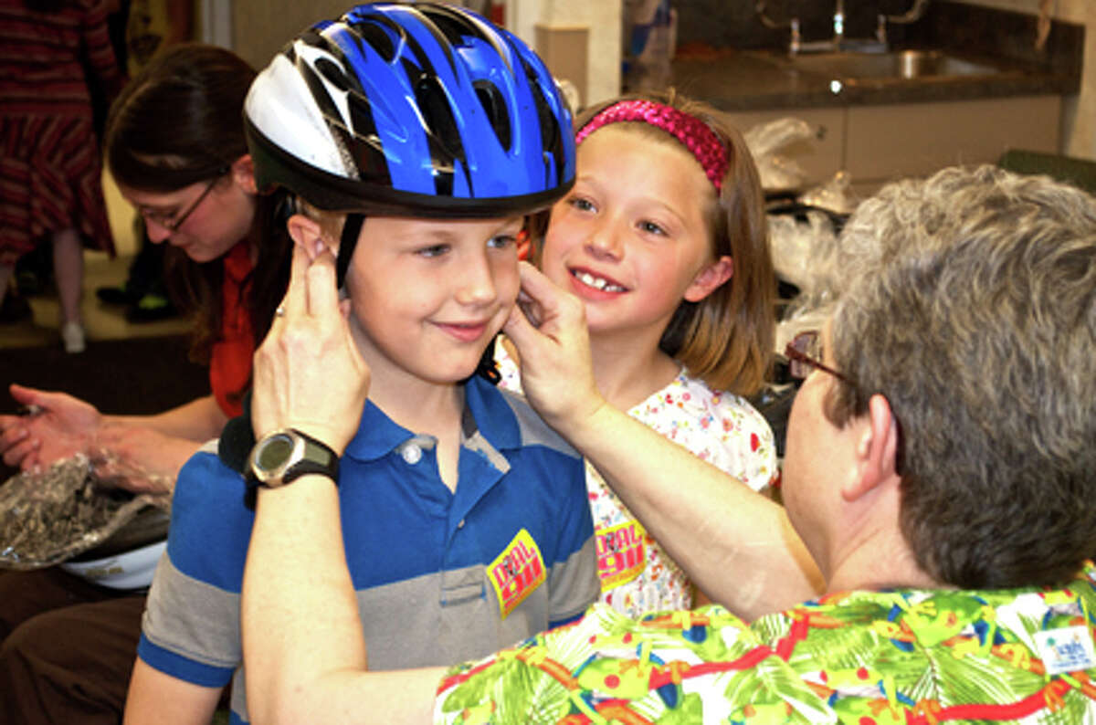 Photo providedEthan Breault of Gladwin is fitted for a bike helmet by Sandra Emmendorfer-Keryk, PTA, while friend Khole Thurlow waits in line at the annual Tot Tours hosted by MidMichigan Medical Center-Gladwin.