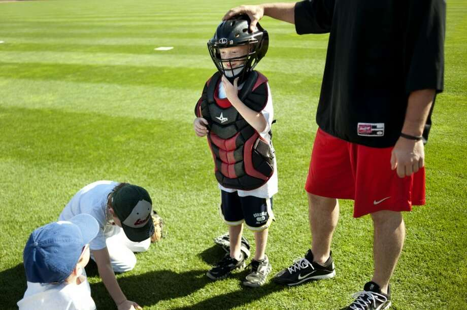 NEIL BLAKE | nblake@mdn.netConnor Moening, 8, of Midland, tries on catcher Pratt Maynard's equipment as Maynard teaches about his position during a two-day baseball camp hosted by the Great Lakes Loons at Dow Diamond last week. The campers were taught pitching, fielding, hitting and throwing by Loons players and their Manager John Shoemaker. Another two-day baseball camp is scheduled for July 25-26. Photo: Neil Blake/Midland  Daily News