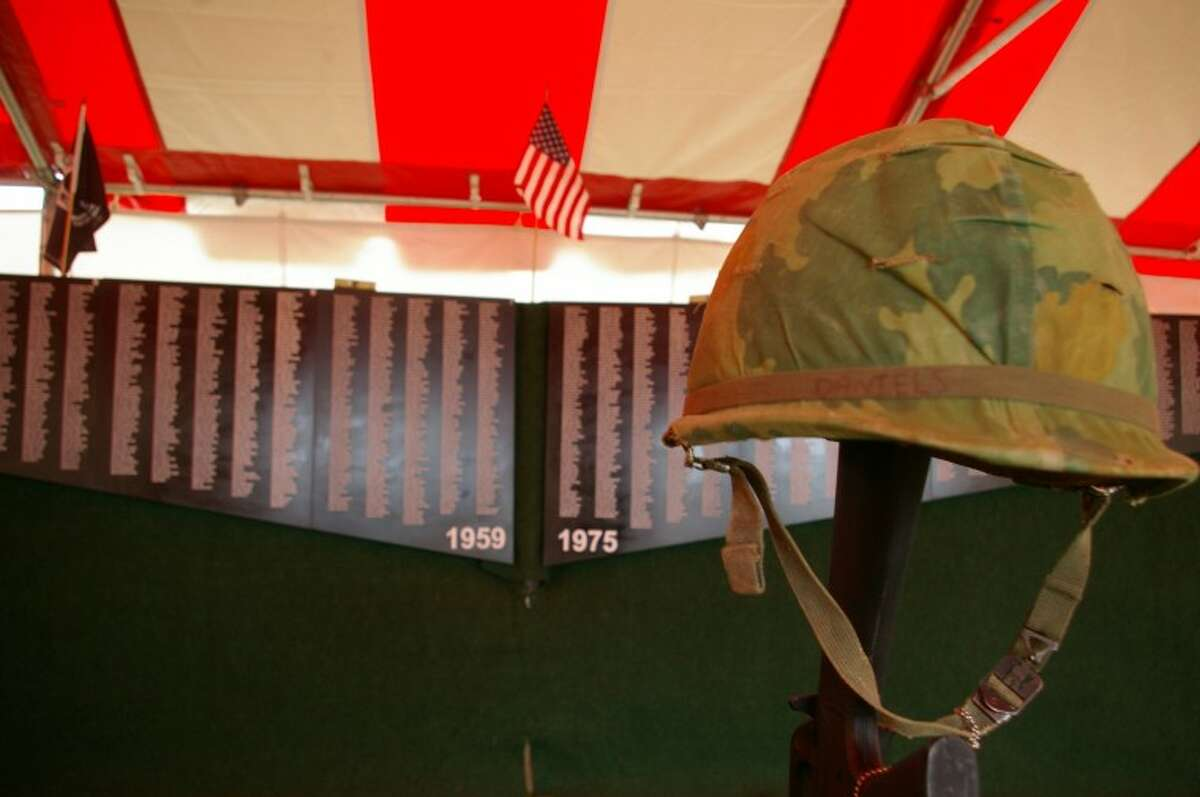 Stuart Frohm   for the Daily NewsThe Michigan Vietnam Memorial Wall is seen behind a Vietnam soldier's helmet, dog tags and an inverted model of an M16 rifle at the Midland County Fairgrounds.