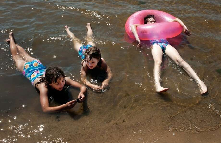 BRITTNEY LOHMILLER   photo@mdn.netFrom left, cousins Adaline Ciehmer, 9, of Auburn, Bethany Honold, 7, of Freeland and Taylor Honold, 9, of Freeland rest in Sanford Lake to keep cool last week. Photo: Brittney Lohmiller