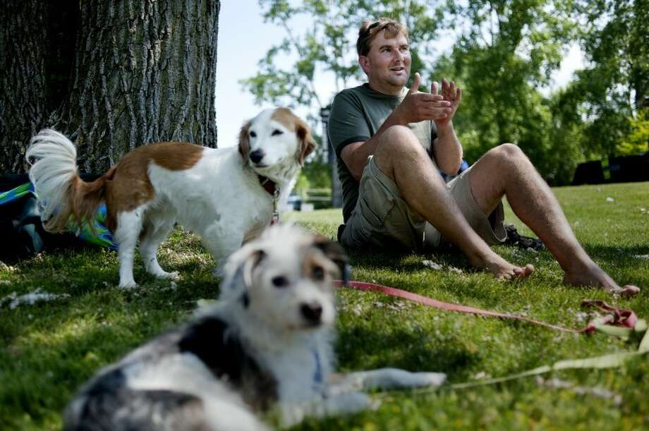 Gladwin resident Greg Allington claps after a song as he and his dogs Eli and Frieda, left, take in the fifth annual Free Music Festival Saturday at Tittabawasee Township Park in Freeland. The music festival featured various genres of music including rock, blues, indie, country, and alternative. Photo: Nick King/Midland  Daily News