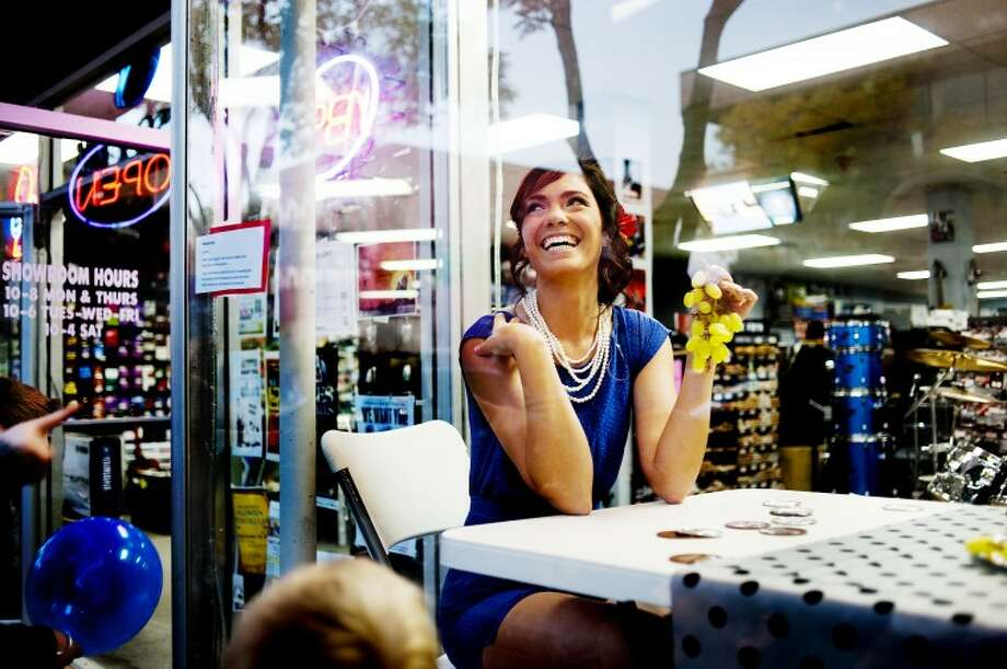 NEIL BLAKE | nblake@mdn.netNorthwood University junior Marina Resto cracks a smile as people make faces  at her as she poses in the window of Mid Michigan Music on Main Street on Thursday during Mannequin Night. The event is put on annually by Northwood's Fashion Department. Photo: Neil Blake