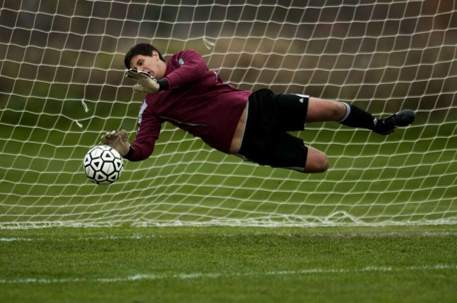 Bullock Creek's goal keeper Timothy Tripp II makes the game winning save against Clare during the second round of penalty kicks after overtime ran out during the district semi final at Standish-Sterling Central High School on Tuesday. Photo: NEIL BLAKE | Nblake@mdn.net