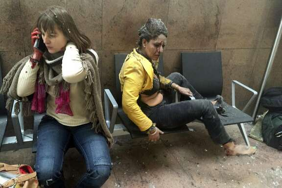 In this photo provided by Georgian Public Broadcaster and photographed by Ketevan Kardava, injured women are seen in Brussels Airport in Brussels, Belgium, after explosions were heard Tuesday, March 22, 2016. A developing situation left a number dead in explosions that ripped through the departure hall at Brussels airport Tuesday, police said. All flights were canceled, arriving planes were being diverted and Belgium's terror alert level was raised to maximum, officials said. (Ketevan Kardava/ Georgian Public Broadcaster via AP)