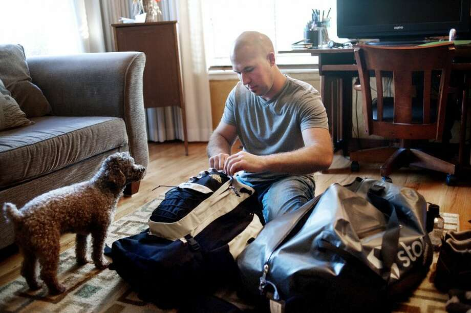 NEIL BLAKE | nblake@mdn.netChris Sushynski of Midland packs his bags in his living room while his dog, Ike, a toy poodle, observes on Thursday. Sushynski has left for a three week trek to base camp on Mount Everest in Nepal, which sits at just over 17,500 feet above sea level. It was on his dream list of things to do, and he decided there was no better time to make it happen. Photo: Neil Blake