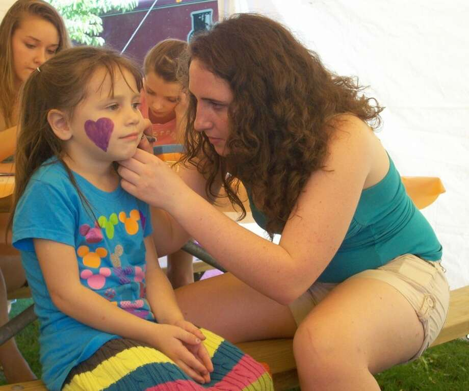 Patti Brandt | for the Daily NewsAva Massey, 5, of Midland, gets her face painted by volunteer Maggie Thompson, a student at Dow High School, at the Be a Tourist in Your Town event.