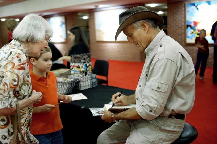 NICK KING | nking@mdn.netJack Hanna, right, signs a book for Sharon Rueterbusch, of Frankenmuth, as her grandson Karl, 8, looks on before Hanna's presentation Thursday at the Midland Center for the Arts. Photo: Nick King/Midland  Daily News