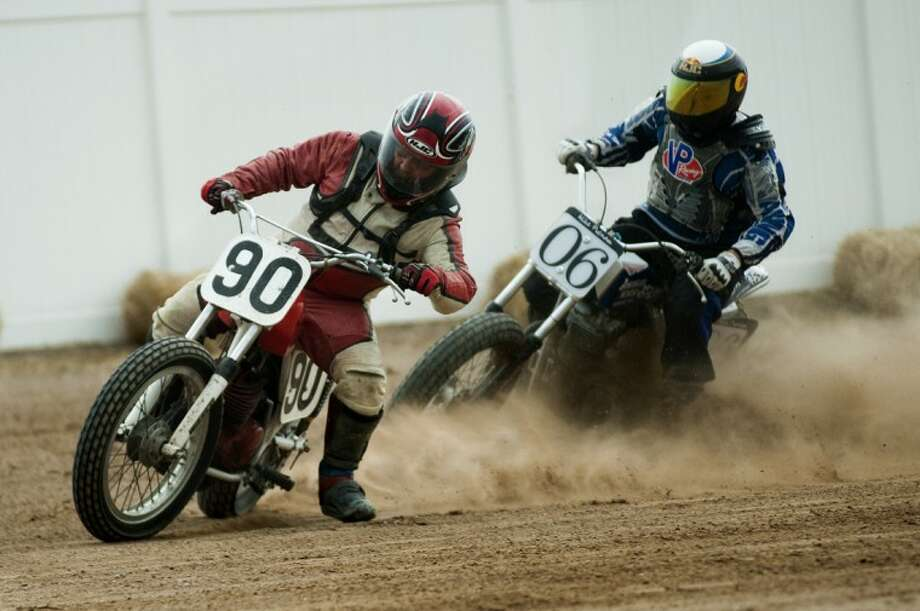NEIL BLAKE | nblake@mdn.netLonnie Vanderpool, left, and Mike Putnam take corner four of a half mile flat track motorcycle race at the Midland County Fairgrounds on Saturday. Photo: Neil Blake/Midland  Daily News