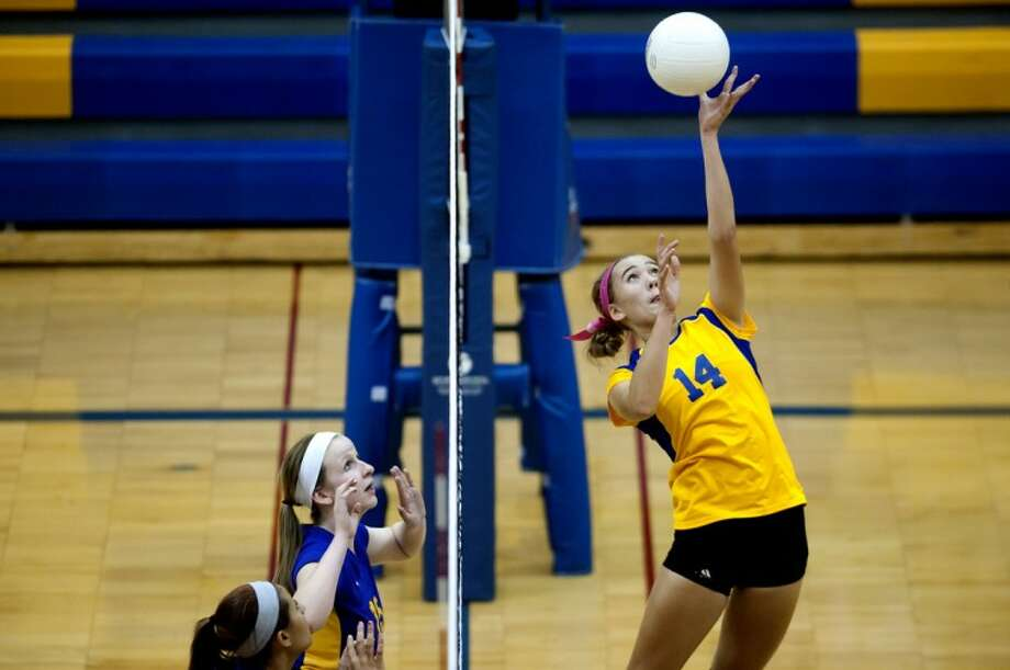 Midland's Mallory Rajewski, right, hits the ball over the net as Bay City Central's Chelsey Dobyne, left, and Saige Tomczak look on during their game Tuesday at Midland High School. Photo: NICK KING | Nking@mdn.net