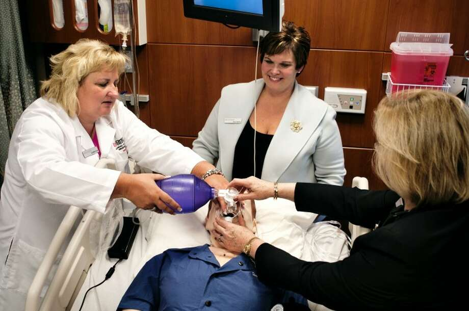 "Davenport University faculty member Lynette Love, left, uses a bag valve mask on ""Sim Man"" with the help of Provost Linda Rinker, right, while nursing faculty member Amy Stahley, center, looks on Monday afternoon at the unveiling of the new simulation labs at the Midland campus. ""'Sim Man' offers students the ability to practice situations they may encounter in a clinical environment in a safe learning environment,"" said Shannon Krolikowski, simulation lab and clinical coordinator. Photo: SEAN PROCTOR 