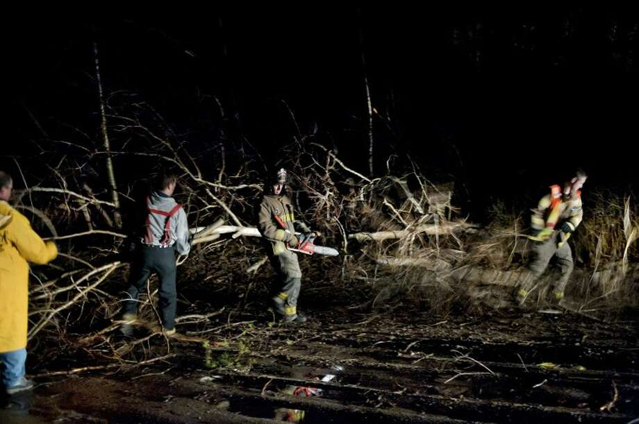 NICK KING | nking@mdn.netColeman firefighters remove a tree that was knocked down and blocking Burns Road near Coleman Monday night after a severe storm moved through the area. Photo: Nick King/Midland  Daily News