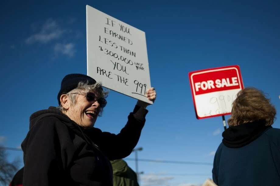 "NEIL BLAKE | nblake@mdn.netEvelyn Lipowitz of Midland smiles as she talks to fellow protesters at the Occupy Midland event in front of the Bank of America on Saginaw Road in Midland. ""I always think it's important for citizens to be active in government,"" Lipowitz said."