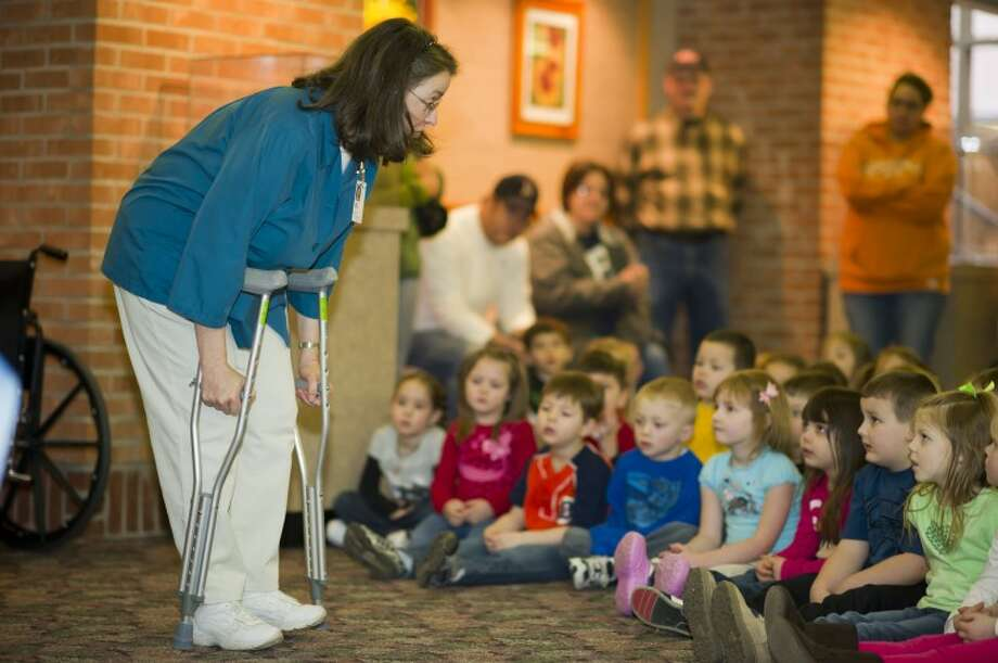 Photo providedLisa Ziettlow, who serves in the guest and patient service and student volunteer service at MidMichigan Medical Center-Midland, shows children attending the Beauregard Bear Health Adventure various equipment they might see or use when visiting the hospital.