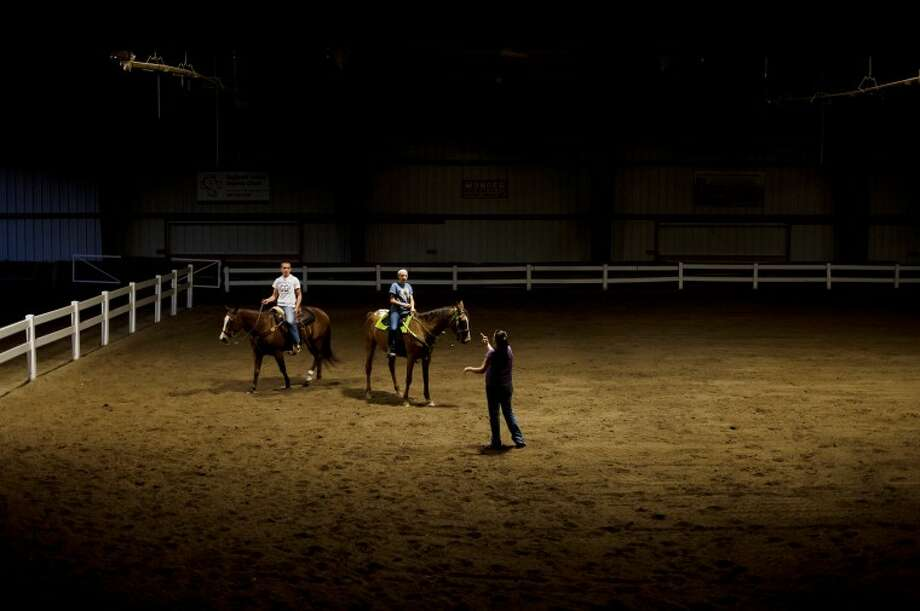 Bullock Creek freshman Brandt Gaffke, left, and sophomore Kim Chapin, center, listen to speed coach Cami Comper atop their horses, Sadie and Sundae respectively, during practice at the Midland County Fairgrounds on Oct. 11.  The practice was their last before the Michigan Interscholastic Horsemanship Association state championship,  which was held at the Midland County Fairgrounds, very familiar terrain to the team who often practice and compete on the same soil. This is the fifth year straight that the team has competed at the state championship.Bullock Creek freshman Brandt Gaffke, left, and sophomore Kim Chapin, center, listen to speed coach Cami Comper atop their horses, Sadie and Sundae respectively, during practice at the Midland County Fairgrounds on Oct. 11.  The practice was their last before the Michigan Interscholastic Horsemanship Association state championship,  which was held at the Midland County Fairgrounds, very familiar terrain to the team who often practice and compete on the same soil. This is the fifth year straight that the team has competed at the state championship. For more photos from the team's season see www.mdnvisuals.com. Photo: By NEIL BLAKE | Nblake@mdn.net