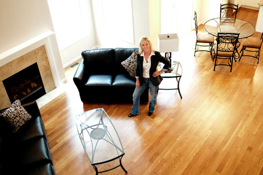Pamela Hagen, of Schroeder Homes, poses in the living room of a spec home in the Countryside Estates subdivision in Midland. Photo: NICK KING | Nking@mdn.net  / Midland Daily News