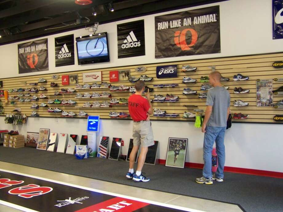 Jennifer Heronema | for the Daily NewsA customer checks out the shoes at the new Runners Performance Store in Midland