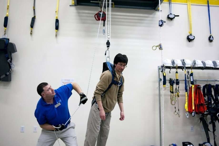 THOMAS SIMONETTI | tsimonetti@mdn.netBrian Huebsch lifts Marc White, senior safety specialist with the Great Lakes Training Center, to demonstrate the use of a suspension trauma strap during a hands-on safety training open house. Photo: Thomas Simonetti