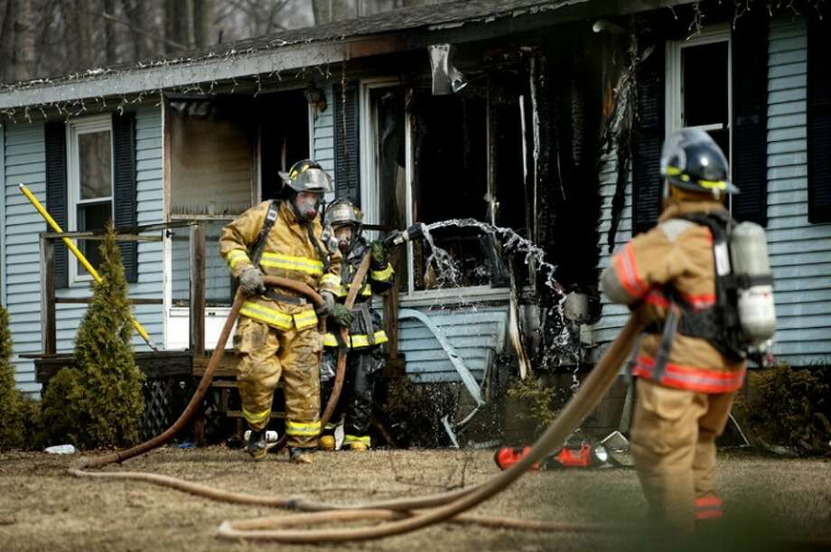 NICK KING | nking@mdn.net Firefighters work to put out a fire that damaged a home Wednesday off North Jefferson Road. Mills and Larkin Township firefighters responded to the blaze. Photo: Nick King/Midland  Daily News