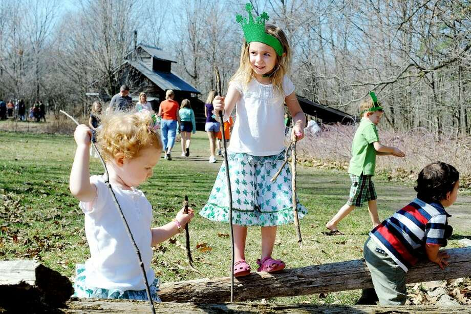 JAKE MAY | for the Daily NewsLily Newton, 2, left, and her sister, Katelynn, 4, both of Midland, play around on a log fence with long walking sticks they found near the Sugarhouse. The girls wore shamrock skirts and a green hat for St. Patrick's Day on Saturday at the Chippewa Nature Center during Maple Syrup Day, where more than 1,700 people toured the facilities, made crafts and saw demonstrations and other activities.