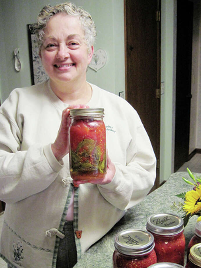 Cindy Crain Newman | for the Daily NewsDonna Frawley cans tomatoes from her backyard garden each year and enhances their flavor by including lots of basil leaves from her garden, too.