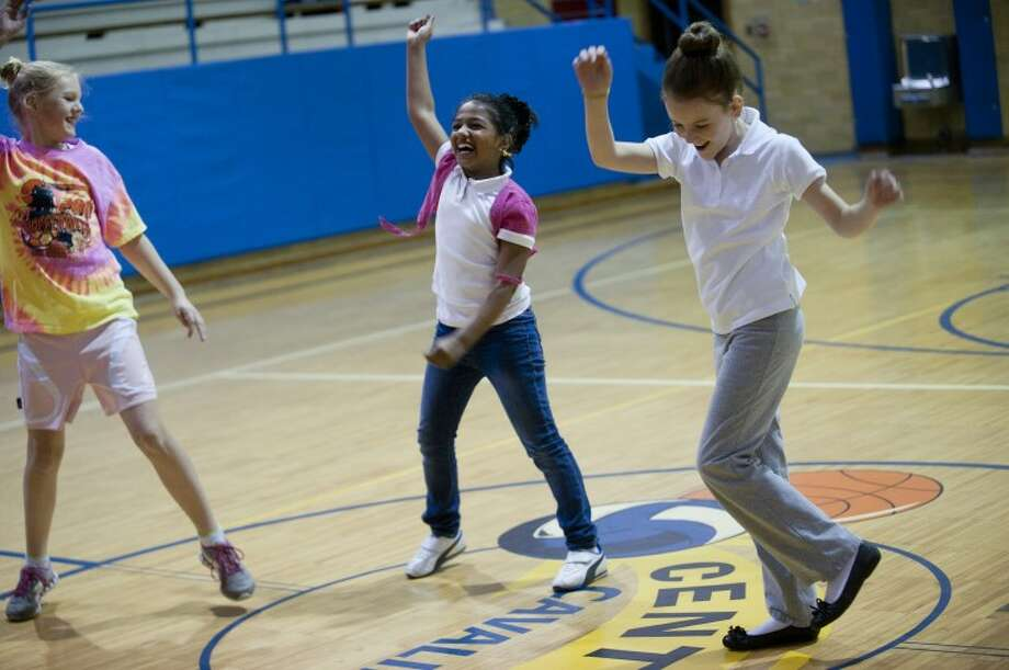 NEIL BLAKE | nblake@mdn.netFifth-graders from St. Brigid Catholic School, Sami Vansumeren, left, Natasha Singareddy and Julia Faught, dance the Zumba, a Latin inspired fitness dance,  at Central Middle School during Fiesta Hispana 2012. The event was for area elementary school fifth-graders and gives them an opportunity to practice their Spanish with native Spanish speakers while learning about Hispanic cultures. Photo: Neil Blake/Midland  Daily News