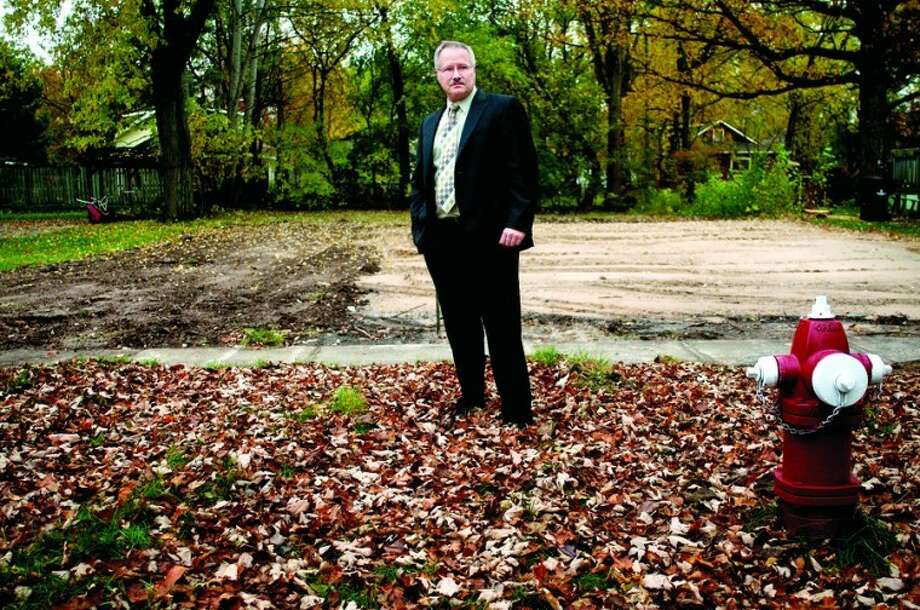 Midland Police Detective Lt. Greg Kramer stands in front of a lot on Mill Street where a house once stood. The home that used to be there was a drug house and was demolished after the occupants were arrested for selling crack cocaine. Photo: Nick King/Midland  Daily News