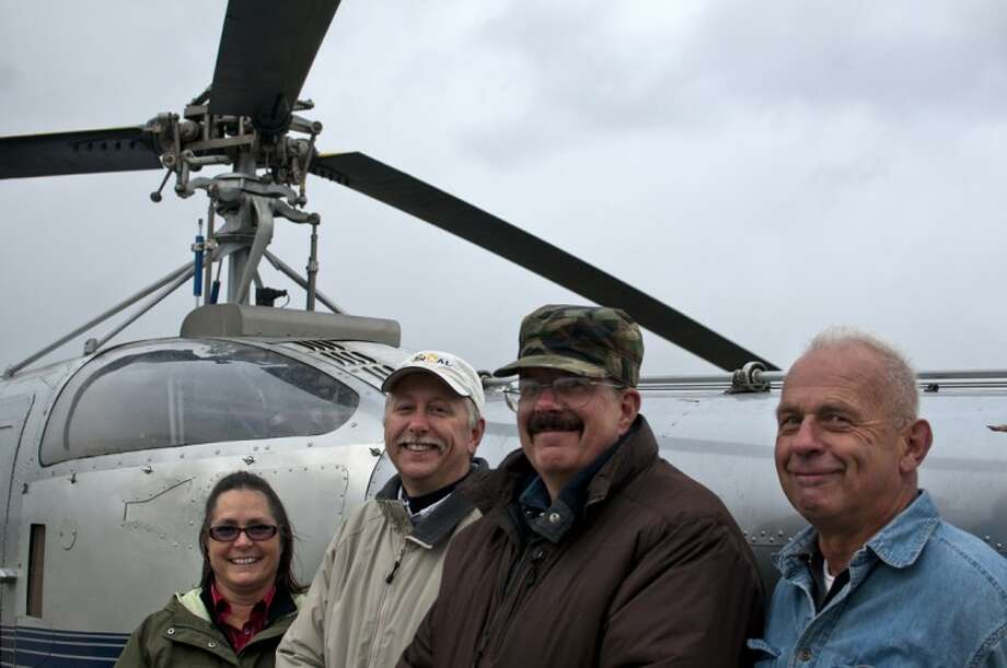 From left, Karen Sheppard, Steve Sheppard, and, far right, Paul Pangborn, all members of a new helicopter club in Midland, pose with their new chopper, a 1952 Sikorsky S-52, at Jack Barstow Airport on Friday. Shown middle right is JT Rairigh, helicopter pilot and airport operator who will train the members. Photo: LIBBY MARCH | For The Daily News