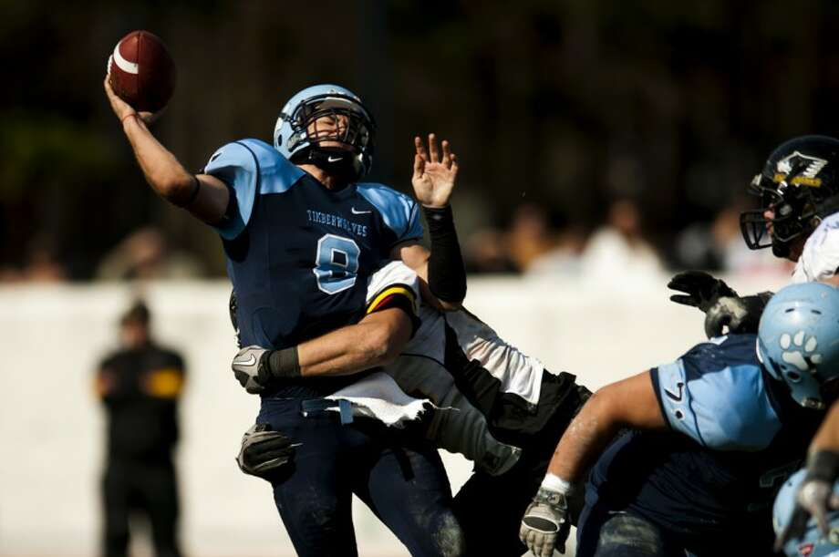 Northwood quarterback Dan Nugent gets wrapped up as he releases the football during Saturday's game against Michigan Tech at Hantz Stadium. Photo: NEIL BLAKE | Nblake@mdn.net