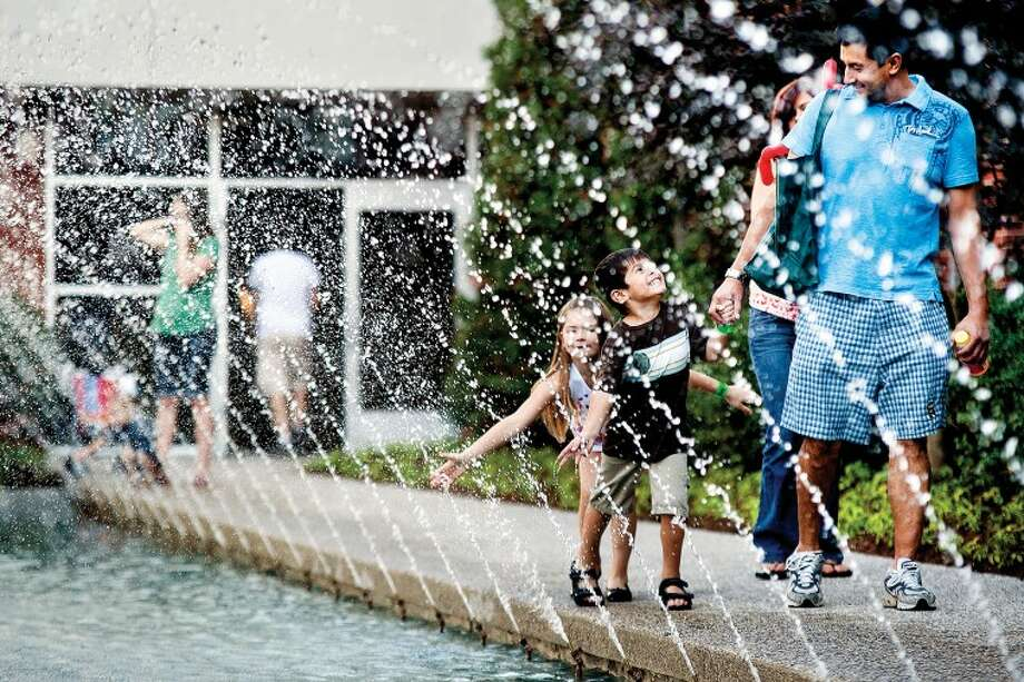 SARA WINKLER | for the Daily NewsCary Lopez, right, of Bay City walks along the shooting streams of a fountain with his son Marcelino, 4, and daughter Tayleigh, 7, in the Delta College courtyard. Lopez and his wife, both students at Delta, brought their children to the main campus for the college's 50th Birthday Open House celebration that included a wide variety of entertainment and activities for attendees.