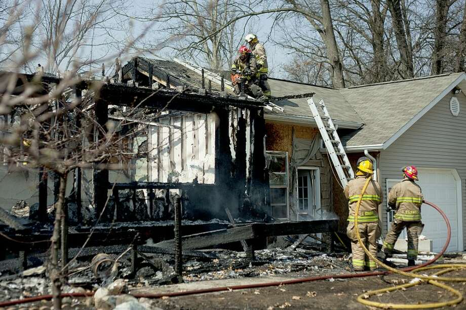 NEIL BLAKE | nblake@mdn.netJerome Township firefighters work to extinguish a blaze that gutted a home on North 11 Mile Road on Thursday afternoon. Photo: Neil Blake/Midland  Daily News