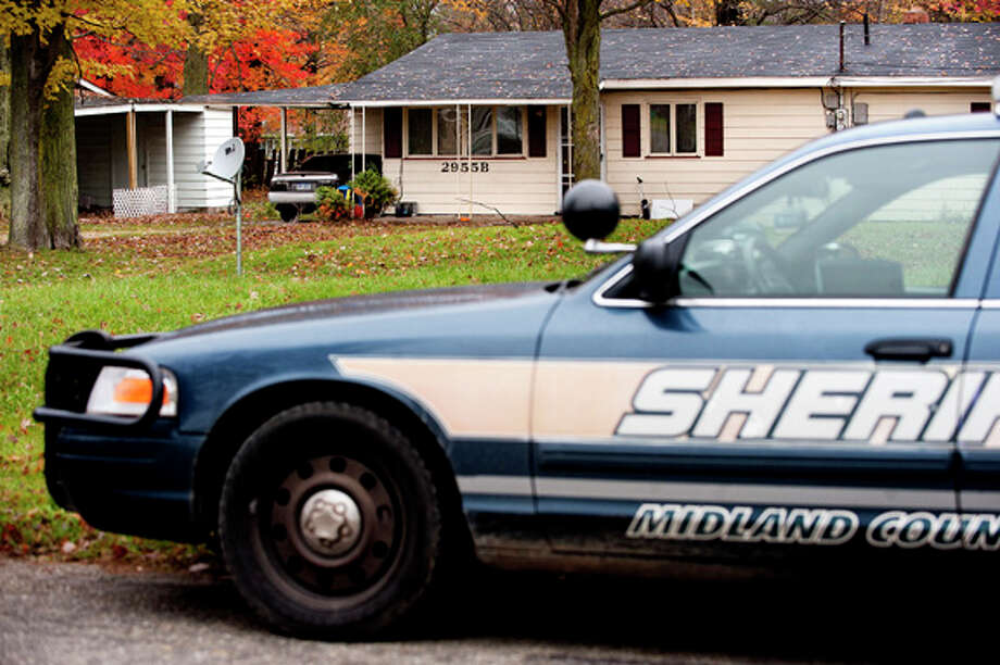 A Midland County Sheriff's patrol car is parked in front of a Yoder Drive home where deputies investigate the circumstances behind the death of a man whose body was found in the front yard. Photo: THOMAS SIMONETTI | Tsimonetti@mdn.net