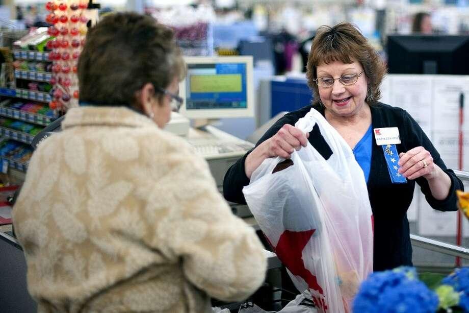 THOMAS SIMONETTI | tsimonetti@mdn.net Kathleen Fortier, right, bags groceries during her job as a cashier at K-Mart in Midland. Photo: Thomas Simonetti