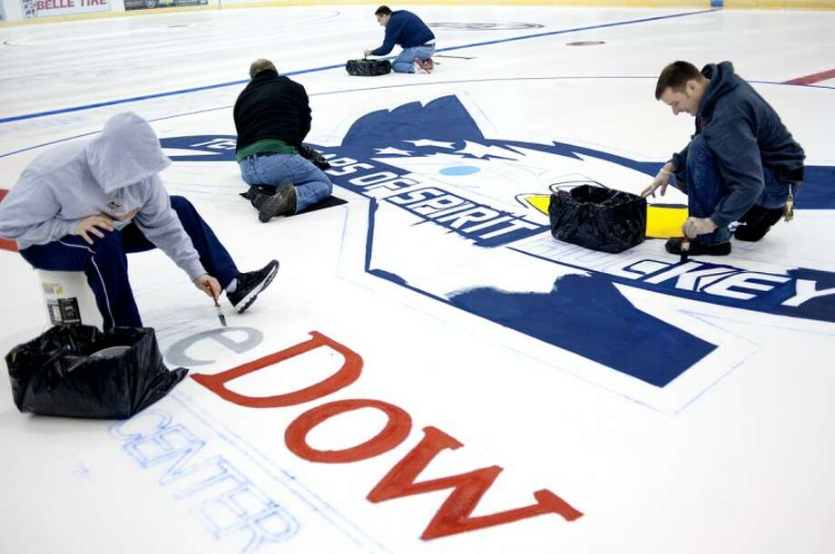 NICK KING | nking@mdn.net From left, Saginaw Spirit equipment manager Brian Allen, director of sales and marketing Rick Riffel, athletic trainer Toby Blossen and Dow Event Center manager Tyler Abbs work on painting the ice Tuesday at the Dow Event Center in Saginaw. The paint job takes about 8 hours with another 72 hours of ice building and preparation before it can be skated on again. Photo: Nick King/Midland  Daily News
