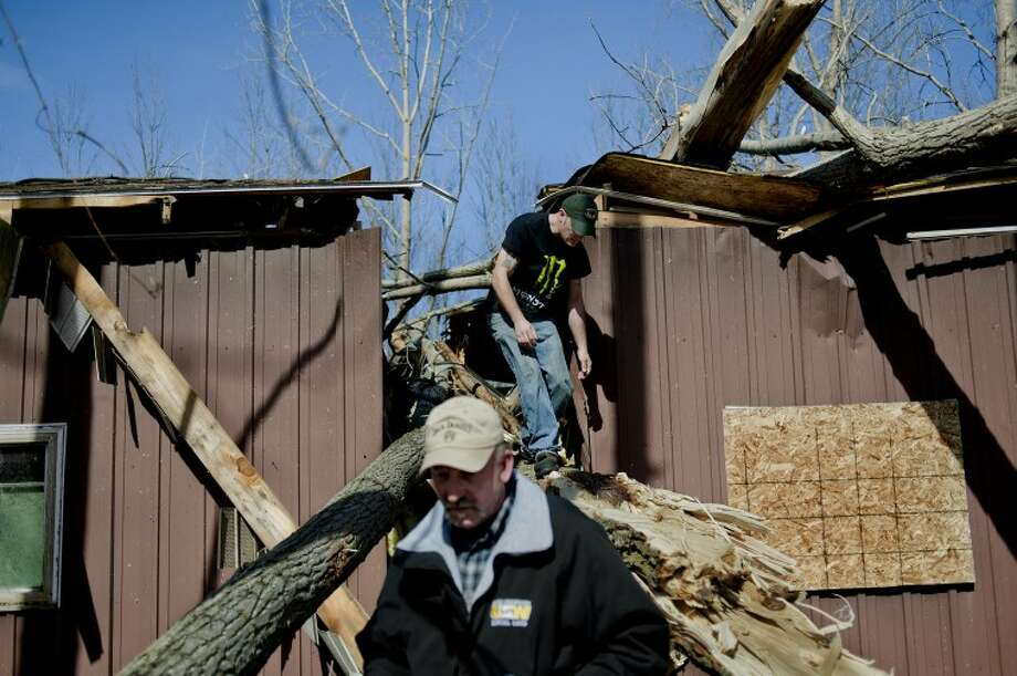 NICK KING | nking@mdn.netMark Kilbreath, left, and his son, Brent, check out the damage to a garage on the property of Mark's parents, Floyd and Mary Kilbreath, on Burns Road near Coleman on Tuesday. A storm that spawned a tornado damaged the area on Monday night. A camper was toppled, trees were uprooted and another structure on the property was damaged by the storm. Floyd and Mary Kilbreath were not hurt and their house suffered minor damage. Photo: Nick King/Midland  Daily News