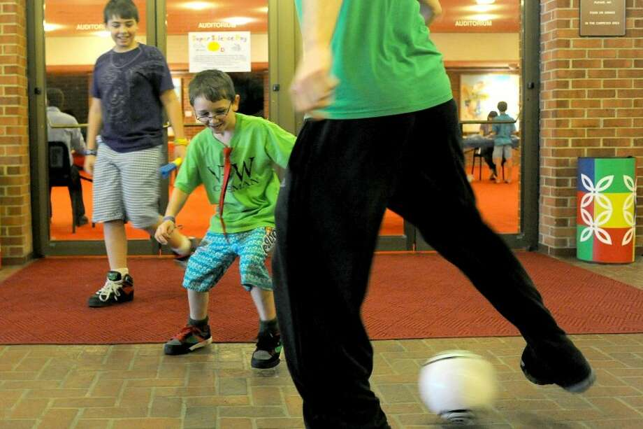 "JAKE MAY | for the Daily NewsDamien Leddy, 11, smiles as he watches his brother, Dakota, 6, both of Coleman, attempt to steal the ball from Keith Lough of Midland, a trainer and assistant coach at the Midland Soccer Club, as they play a game of keep away with a soccer ball Saturday at the Midland Center for the Arts during Summer Camp Kick-Off. The event allowed children and parents to learn about 24 summer camp opportunities. Neither Leddy brother had played soccer before Saturday. ""Soccer teaches the kids discipline, time management, but also keeps them active and they make friends,"" Lough said."