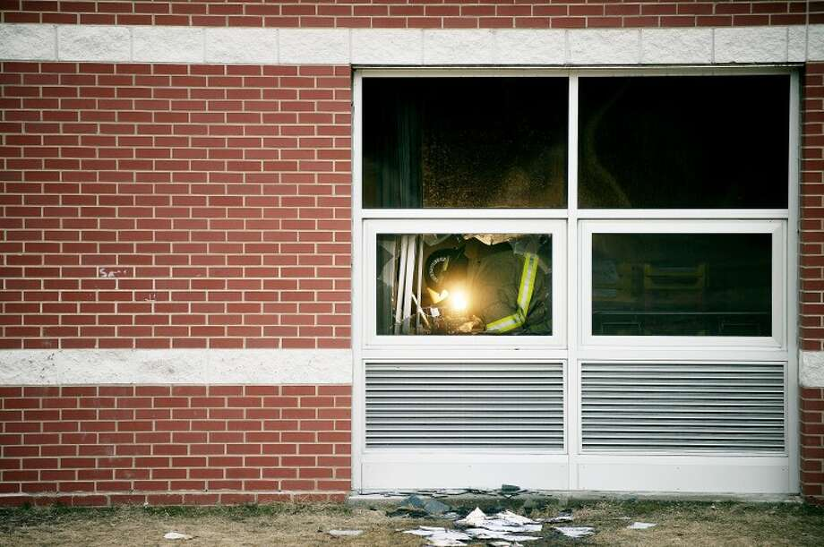 NICK KING | nking@mdn.net A firefighter is seen in the broken window where police believe the suspect broke into the school on Wednesday morning. One classroom was damaged by the fire. School was closed for two days during the investigation and cleanup. A reward is being offered for information. Photo: Nick King/Midland  Daily News