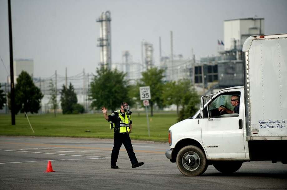 NICK KING | nking@mdn.netMidland Police Officer Darin Updike redirects traffic on South Saginaw Road, which was closed after a chemical release at Dow Corning Corp. this morning in Midland. The chemical release closed Saginaw Road between Mark Putnam Drive and Salzburg Road for about an hour. Updike said he was wearing the protective mask as a precautionary measure.
