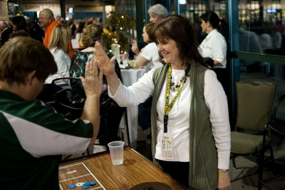 THOMAS SIMONETTI | tsimonetti@mdn.net Dow pom coach Colleen Rabine, center, high fives Beth Whelan at the Big Wheel, a game at the inaugural Booster Bash at Dow Diamond on Friday. Photo: Thomas Simonetti
