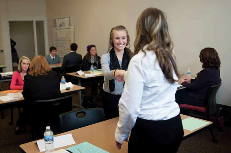 """Midland High junior Emily Burrell, left, greets Chemical Bank Administrative Assistant Ashlie Kreger before starting a mock interview at Davenport University on Tuesday. Burrell was one of hundreds of Midland County students to go through the annual """"Ready, Set, GET HIRED!"""" program which strives to prepares students for their first interviews. Photo: NEIL BLAKE 